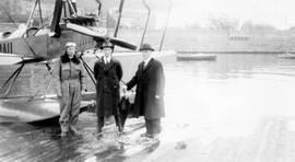 First air mail Victoria to Seattle, pictured are Eddie Hubbard and Postmaster Bishop with umbrella