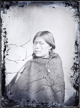 Studio portrait (side profile, mid-length) of an unidentified Indigenous individual seated taken at a photographic studio attributed to Frederick Dally.
