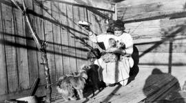 Emily Carr with her pets, Woo, the monkey on her right shoulder; dogs Koko and Ginger Pop; and Ad...