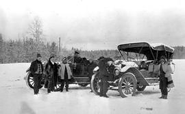 Two early autmobiles and their passengers stopped on the Cariboo Road near 105 Mile House.