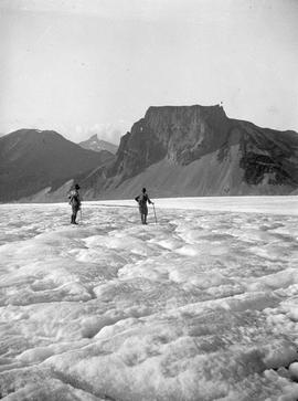 Two roped climbers on a glacier; the Table and Black Tusk peaks in the background; Garibaldi; box 36.