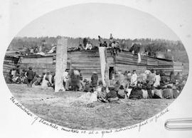 Indians at a Potlach [potlatch].  Songish [Songhees] tribe.  The distribution of blankets, muskets etc. at a grand distribution feast or potlach.""