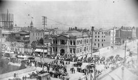 A parade travelling west on Yates Street, crossing Blanshard Street; Carnegie library at centre
