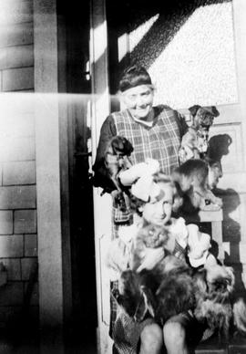 Emily Carr with with neighbour Phyllis Hudson, three dogs, a cat, and her monkey, Woo.