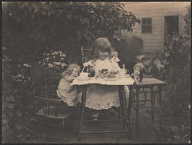 A little girl and her dolls enjoying a tea party