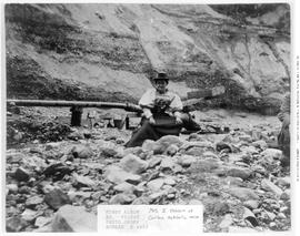Mrs. J.B. Hobson sitting in front of an hydraulic monitor at the No. 1 pit of the Cariboo Hydraulic Mine.