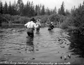 Oil claim survey, Flathead; survey crew wading Beaver Lake.