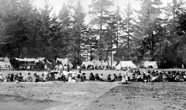 Camp scene, natives seated in circle at Esquimalt potlatch.