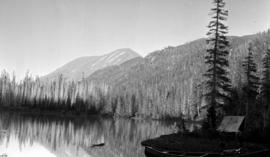 Cosgrove Lake and Smaby Pass; a trapper's cabin behind the canoe.