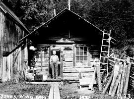 Harry Jones in front of cabin, Wingdam