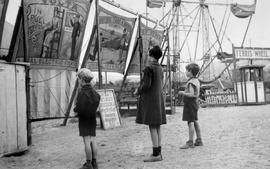 Kamloops Museum photo; Kamloops Fall Fair; children looking at sideshow posters in the midway. Ka...