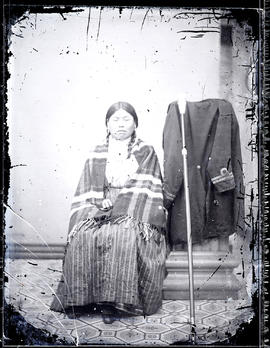 Studio portrait (full-length) of an Indigenous sitter taken at a photographic studio attributed to Charles Gentile studio.