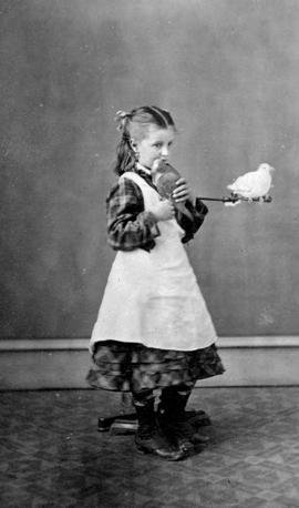 """Lillie"" Maynard standing holding bird; another bird on posing stand."