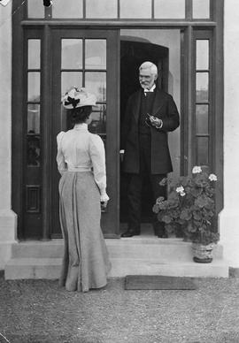Mr. B.W. Pearse greeting a young woman at the door of his home, Fernwood; Victoria, BC.