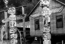 Totem poles in front of a house at Alert Bay, BC.
