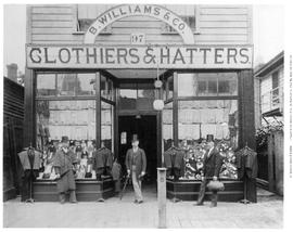 """B. Williams & Co., Clothier & Hatter""; men posing outside shop in Victoria."