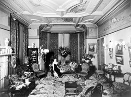 Mrs. Baker and her pug dog with Miss Jean Ross in the drawing room of the Edgar Crow Baker's...