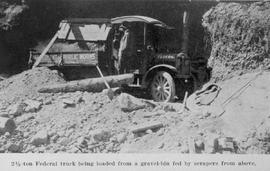 """2 1/2 ton Federal truck being loaded from a gravel-bin fed by scrapers from above."""