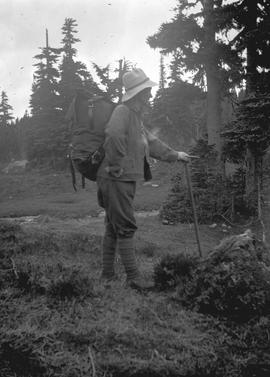 A female climber, possibly Esmee (Betty) McCallum, with pack and ice axe at what may be Garibaldi...