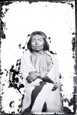 Studio portrait (mid-length) of an unidentified Indigenous individual seated and  taken at a photographic studio attributed to Frederick Dally