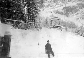 A man in the snow beside a tramway.