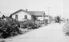 """Parksville, BC""; appears to consist of a tea room, a garage and a church on an unpaved road."
