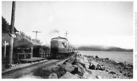 gas-electric car no. 104, 3/4 left, almost head-on, with trailers, mid-distance, at Weston, BC st...