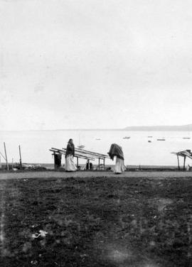 Two native women walking along the beach-front at Skidegate