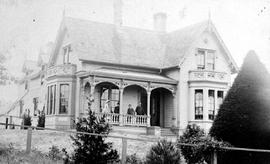 Alex Munro residence, corner of Douglas and Michigan Streets, Victoria; family members [?] posed on porch.