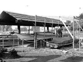 A dugout canoe under construction beside the Tilikum in Thunderbird Park, Victoria.