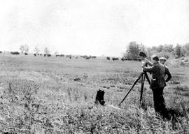 Filmmaker A.D. Kean and his assistant J.R. Nesbit, holding cap, film a buffalo herd in Buffalo Na...