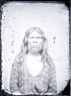 Studio portrait (mid-length) of an unidentified Indigenous individual seated taken at a photographic studio attributed to Frederick Dally.