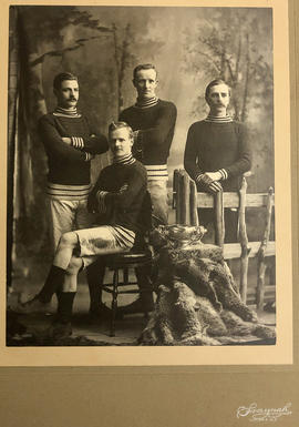 Group portrait of four men in matching sports uniforms