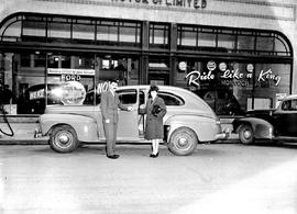 Couple posed outside National Motors Ltd., Ford Monarch dealership, 819 Yates Street, Victoria.