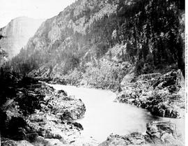 Three Mile Canon [canyon] on the Fraser River, B.C.  The wagon road.  Poles for drying salmon on.