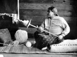 A First Nations woman spinning wool