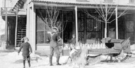 Mike Hintz delivering milk by sleigh; in front of the Arlington Hotel, Trail.