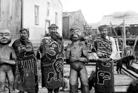 Three men at Alert Bay, BC, wearing button blankets, shown standing with carved figures