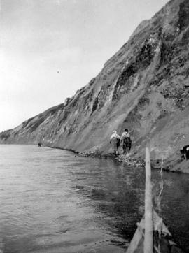 Two men shown tacking up the banks of the Peace River.