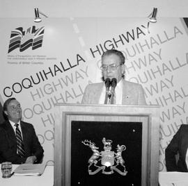 Alex Fraser, Minister of Transportation and Highways, at the podium, making an announcement about...