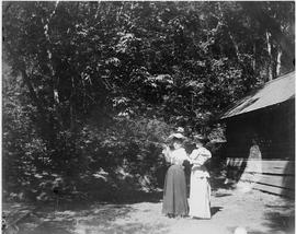 Two women outside a cabin, one is aiming a rifle